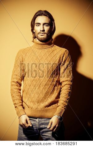 Handsome man wearing yellow pullover. Men's beauty, fashion. Hairstyle for men. Yellow background.