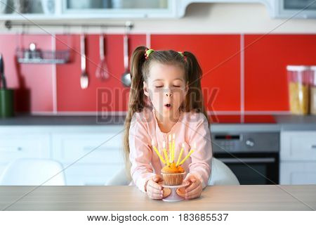 Cute little girl blowing out candles on birthday cake in kitchen