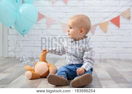 Cute baby boy sitting on floor with teddy bear
