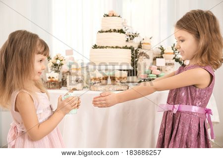 Cute girl giving tasty dessert to her friend at party