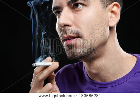 Young man smoking cigarette on black background