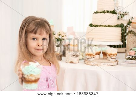 Cute girl with dessert near table served for party