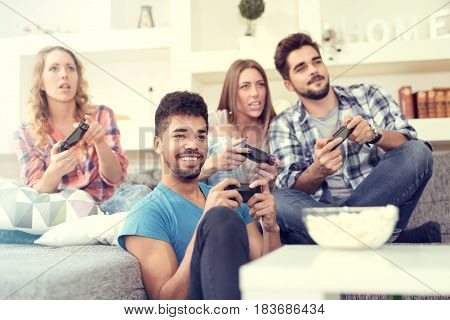 Group of friends having fun and play video games together.