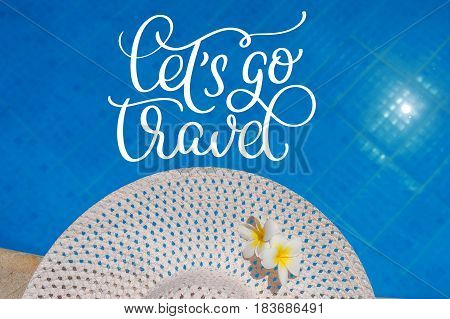Big white hat on the edge of the pool and text Lets go travel. Calligraphy lettering hand draw.