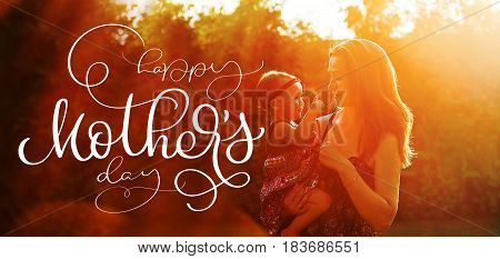 Happy young mother with daughter in front of sun rays and text Happy mothers day. Calligraphy lettering hand draw.