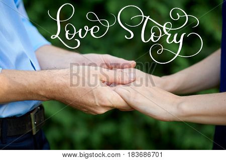 man is holding a woman hands for a walk in a summer park and vintage text Love story. Calligraphy lettering hand draw.