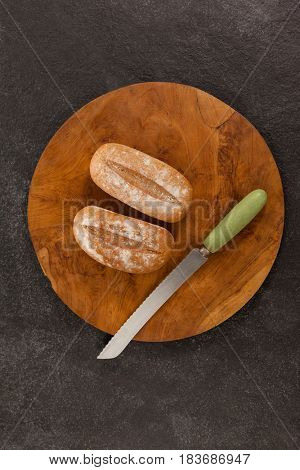 Close-up of two bread loaves on cutting board with knife