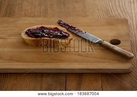 Bread with jam and knife on cutting board