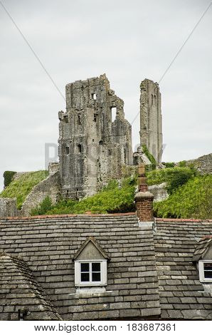Corfe Castle with village roofs in foreground