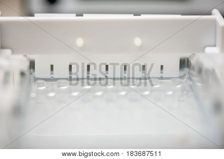 Close-up detail of a electrophoresis comb in an mold filled with agarose gel undergoing solidification. Molecular genetics and medical diagnosis technology concept. poster