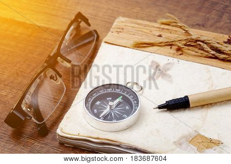 Old vintage retro compass with a book and glasses on wooden background Travel concept background.