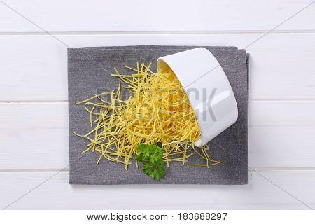 heap of soup noodles spilt out on grey place mat