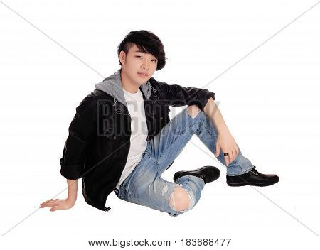 An young Asian teenager sitting in a black leather jacket and ripped jeans on the floor isolated for white background.