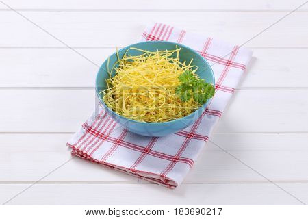 bowl of dry soup noodles on checkered dishtowel