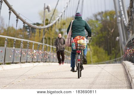 MAGDEBURG, GERMANY - APRIL 22, 2017: cyclist and pedestrian on a suspension bridge over the river Elbe in Magdeburg. The bridge was built in 1999 on the occasion of the Federal Garden Show in Magdeburg