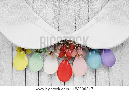 Colorful glass necklace over striped white blouse closeup
