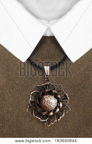 Vintage bronze pendant over brown pullover with white collar closeup