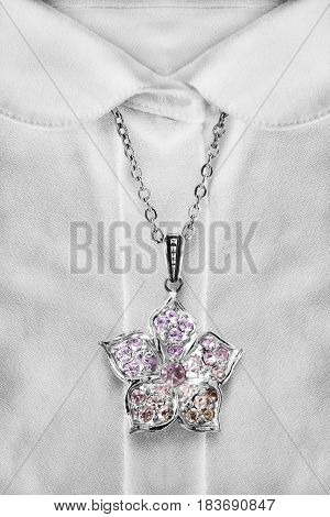 Silver flower pendant with crystals over white blouse closeup