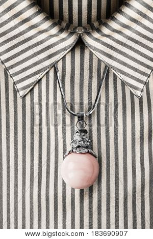 Pink pearl pendant over satin striped blouse closeup