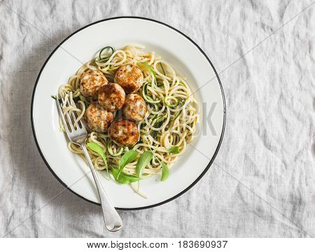 Spaghetti with cheesy chicken meatballs and zucchini noodles. Delicious lunch on a light background top view
