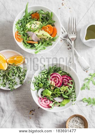 Rocket beets avocados carrots seeds nuts detox salad with orange dressing on a light background top view. Vegetarian healthy eating concept