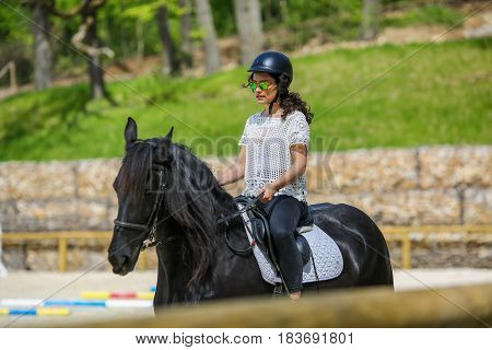 Lovely young brunette riding a horse near forest