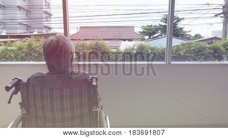 Lonely Senior Looking Through Window In Building - Age, Loneliness And People Concept