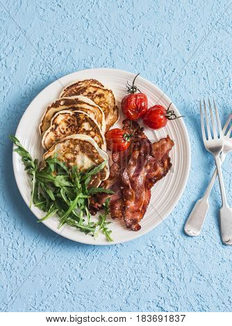 Traditional american breakfast - crispy bacon pancakes with maple syrup roasted tomatoes arugula. On a blue background top view