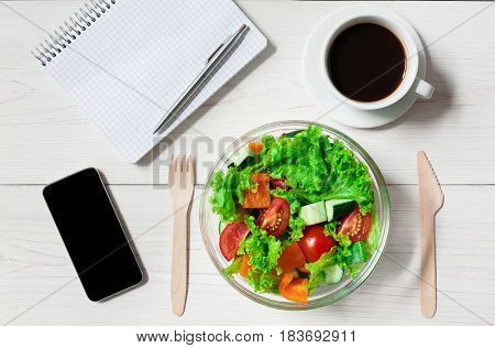 Healthy lunch in office, diet concept. Salad at workplace near mobile and notebook, top view at white wood background
