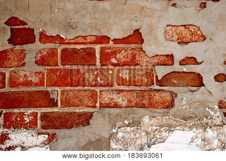Abandoned brick wall partially covered with gray cement plaster, half painted wall foe banner
