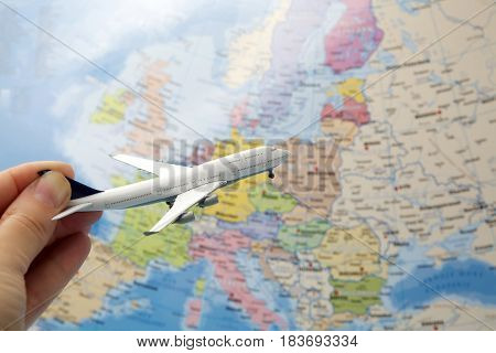 Woman hand holding miniature airplane on map background