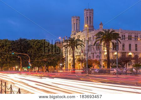 Cagliari, Sardinia - January 2 of 2016, Italy: Town Hall, Municipio di Cagliari also known as Palazzo Vivanet, evening view of The Street of Rome with traffic light trails