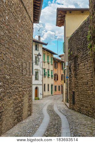 View through narrow, medieval Italian street, Cividale del Friuli, Italy