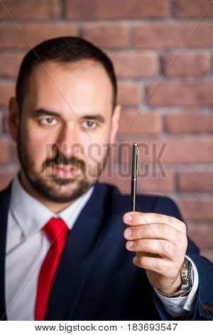 Businessman In Red Tie Is Looking At The Pen