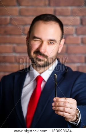 Businessman Winks And Offers To Take A Pen