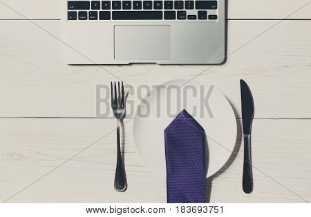 Diet or lack of money concept - no food at business lunch in the office. Top view of working space at white wooden desk, empty plate with tie and cutlery near laptop