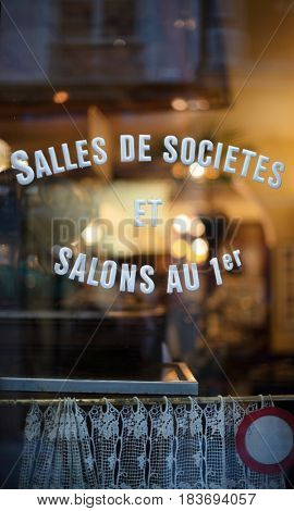 Old French bar with stenciled sign on window, Translation: meeting rooms on first floor