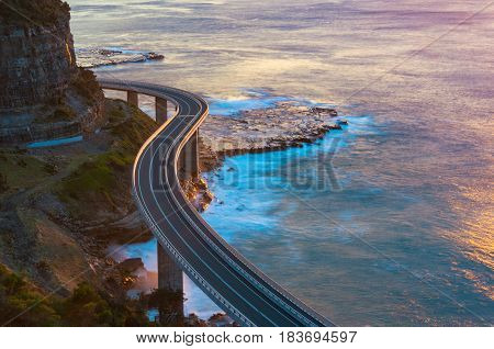 Aerial View Of Bridge Along Cliff Edge And Ocean