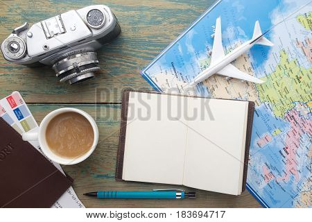 Travel , trip vacation, tourism mockup - close up note book, vintage camera, toy airplane and touristic map on wooden table. Empty space you can place your text or information.