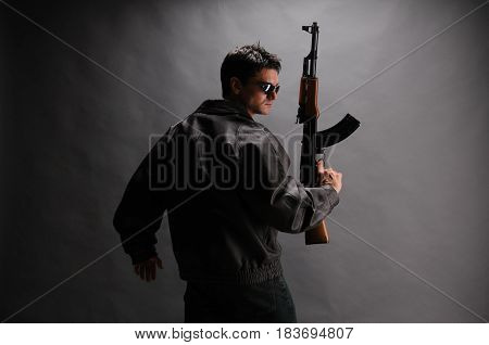 The man is wearing a big jacket and holds a rifle.