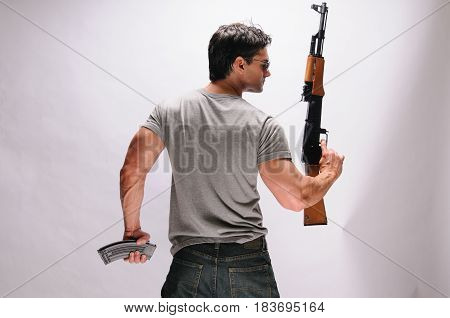 The strong muscle man is holding up his weapon.