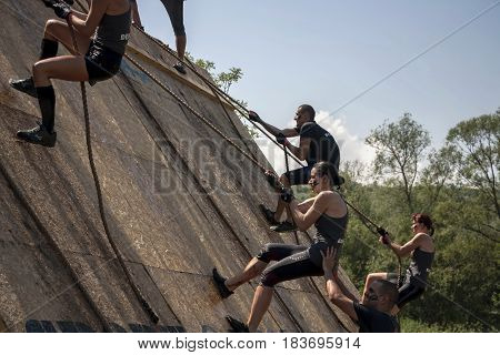 Team Of Men And Women Climbing A Wall With Ropes