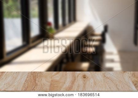 Blur coffee shop or cafe restaurant interior with selected focus wood table for montage or display your product