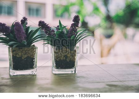 Artificial Flower In Small Glass Pot On A Wooden Table.