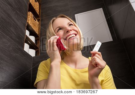 A beautiful young blonde woman sits in the bathroom and holds a positive pregnancy test and red mobile phone. Conceptual photography.