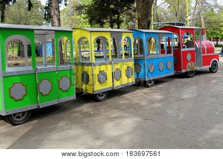 Children's train. Train for children and their parents. Bright, colorful and attracts attention:yellow, blue, red wagons can accommodate many wanting to go.
