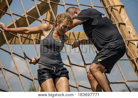 A Woman And A Man Climbing Down A Cargo Net
