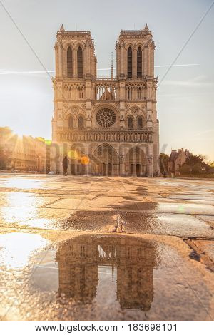 Paris, Notre Dame Cathedral With Reflection In Water Against Sunrise In France