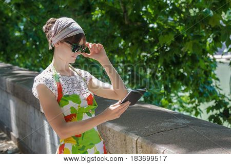 Tourist girl is looking at touchscreen of tablet computer on tree summer city avenue