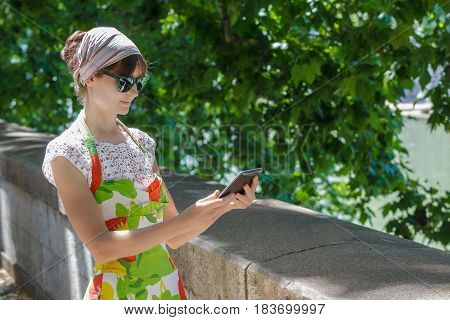 Tourist girl is touching screen of tablet computer on green city alley